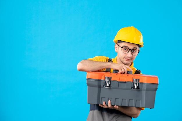 Vista frontale del lavoratore di sesso maschile in uniforme e casco con cassetta degli attrezzi nelle sue mani sull'azzurro