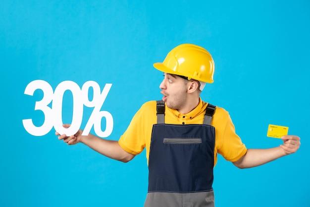 Vista frontale del lavoratore di sesso maschile in uniforme con scritta e carta di credito blu Foto Premium