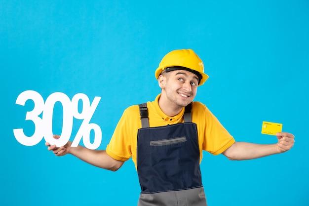 Vista frontale lavoratore maschio in divisa con scritta e carta di credito blu