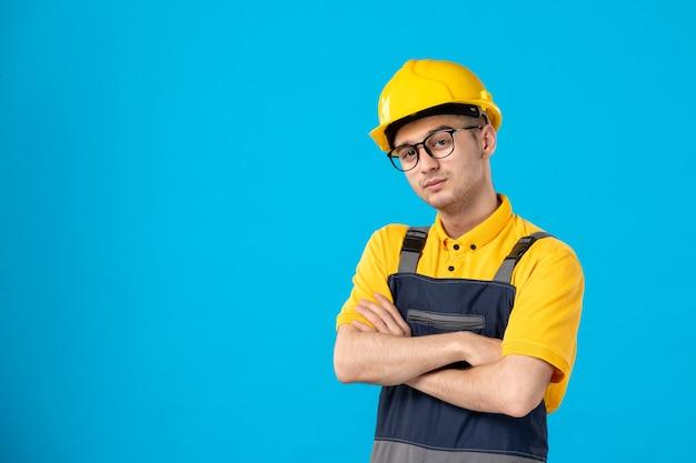 Operaio maschio di vista frontale in uniforme gialla sull'azzurro