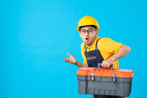 Vista frontale del lavoratore di sesso maschile in uniforme gialla che trasportano cassetta degli attrezzi sul blu