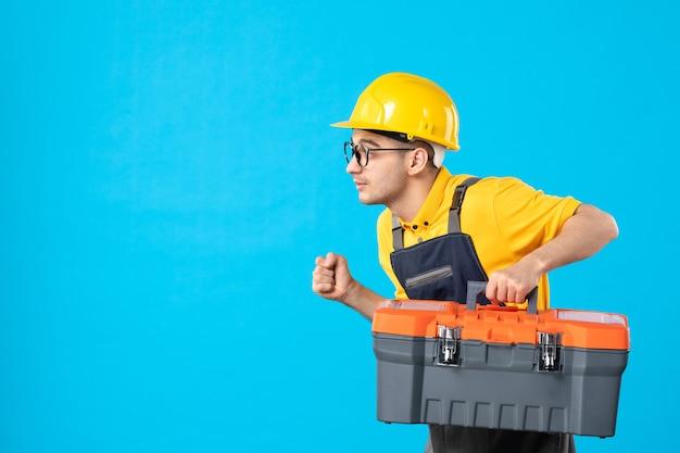Operaio maschio vista frontale in uniforme gialla con cassetta degli attrezzi che si affretta a lavorare su un blu