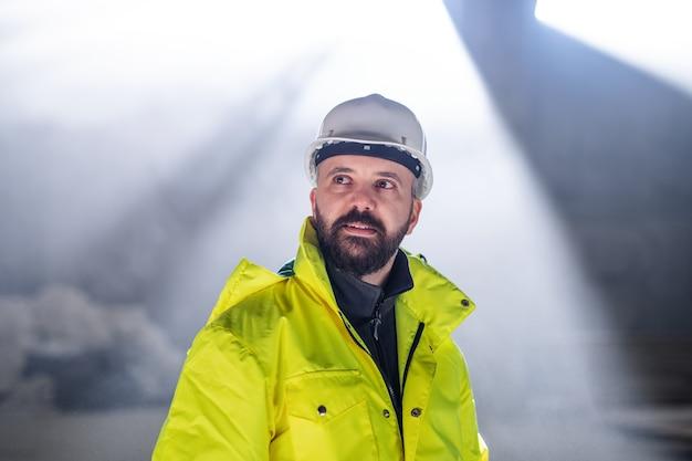Vista frontale dell'ingegnere dell'uomo in piedi sul cantiere.