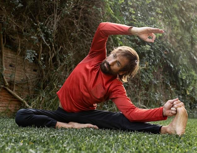 Vista frontale dell'uomo sull'erba all'aperto che fa yoga