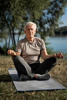 Vista frontale dell'uomo a praticare yoga all'aperto