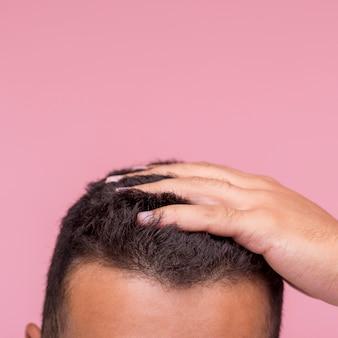 Vista frontale dell'uomo che esegue le sue dita tra i capelli con lo spazio della copia