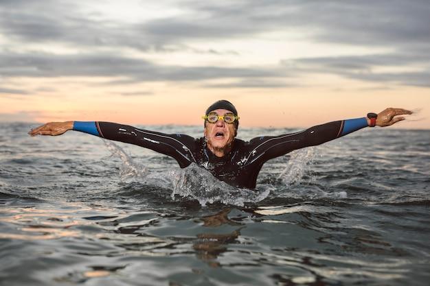 Colpo medio di nuoto dell'uomo di vista frontale