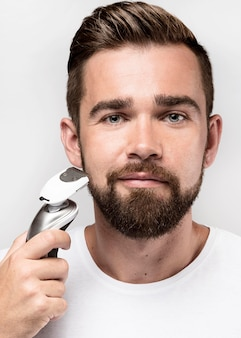 Uomo di vista frontale utilizzando una macchina da barba