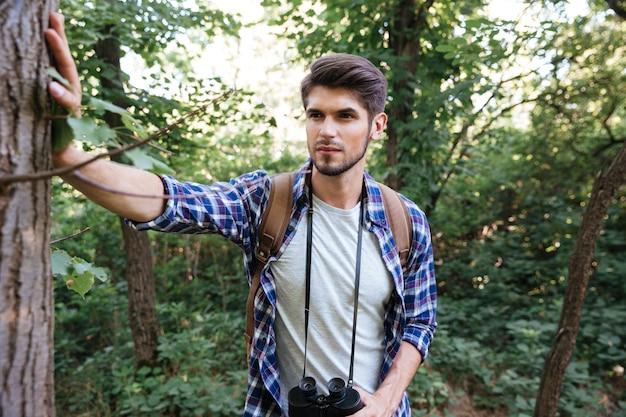 Vista frontale dell'uomo con lo zaino nella foresta