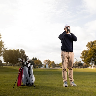 Vista frontale dell'uomo con il binocolo sul campo da golf