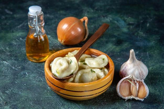 Gnocchi di carne vista frontale all'interno del piatto di legno con olio cipolla e aglio sulla superficie scura