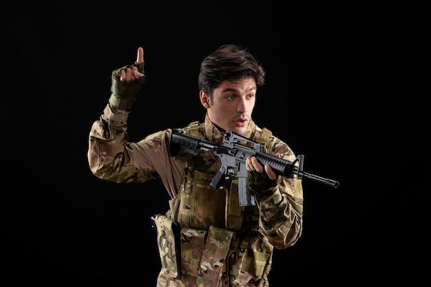 Vista frontale del militare in uniforme che punta il suo fucile in studio su superficie nera