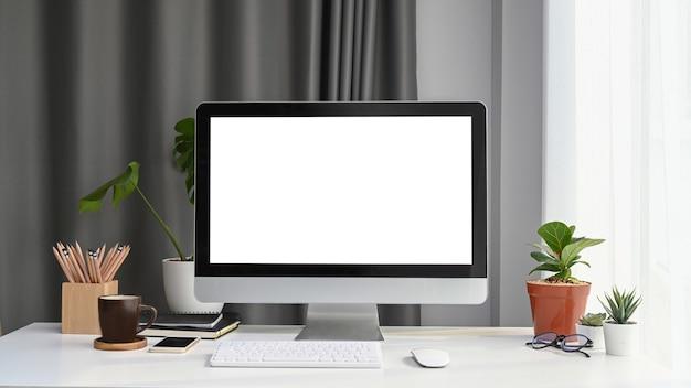 Vista frontale del computer simulato con schermo vuoto, pianta domestica e forniture per ufficio sulla scrivania bianca.
