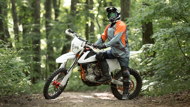 Vista frontale del motociclista in posa nella foresta