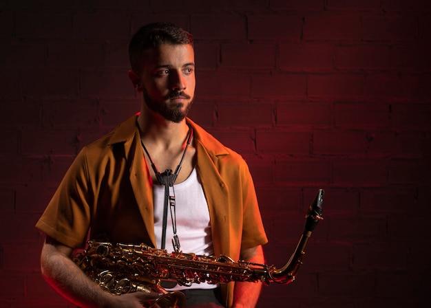 Vista frontale del musicista che tiene un sassofono