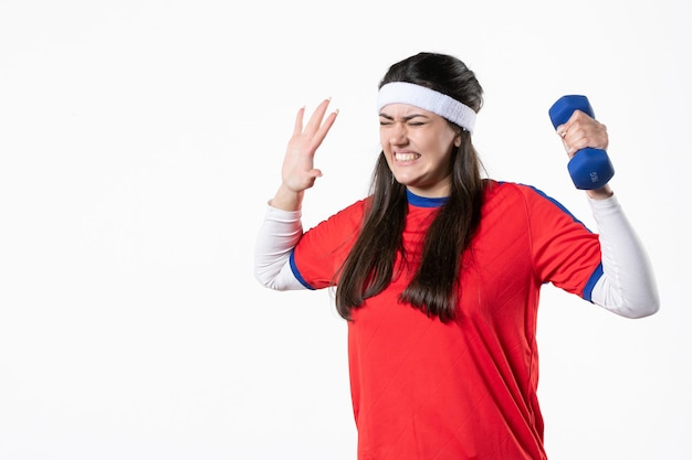 Vista frontale nervosa giovane femmina in abiti sportivi con manubri blu