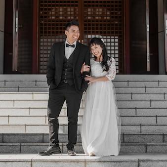 Vista frontale degli sposi in posa insieme sui gradini