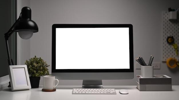 Vista frontale della scrivania da ufficio con computer vuoto e vari strumenti di ufficio sul tavolo bianco.