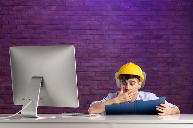 Impiegato di vista frontale dietro la scrivania che lavora con i documenti