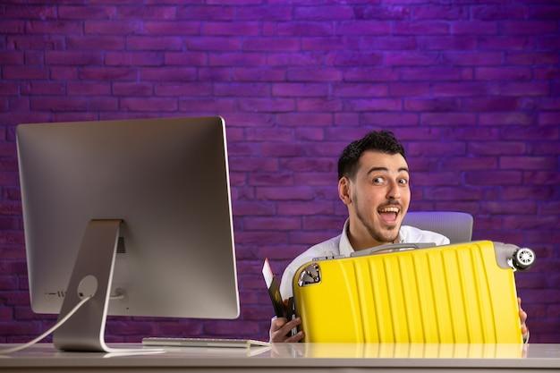 Impiegato di vista frontale che si siede dietro il suo posto di lavoro che tiene biglietti e passaporto