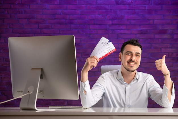 Impiegato di vista frontale che si siede dietro il suo posto di lavoro e che tiene i biglietti