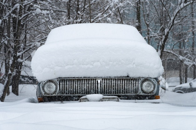 Vista frontale di una vecchia automobile sovietica ricoperta di neve dopo la tempesta di neve nel cortile di mosca