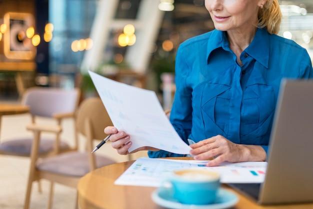 Vista frontale della donna più anziana di affari che si occupa di documenti