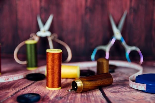 Vista frontale delle bobine di filato arancione e verde. sullo sfondo forbici da cucito vintage su sfondo rosso