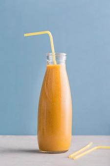 Bottiglia di frullato arancione vista frontale con paglia