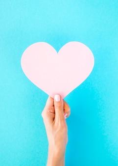 Vista frontale del cuore di carta tenuto a mano