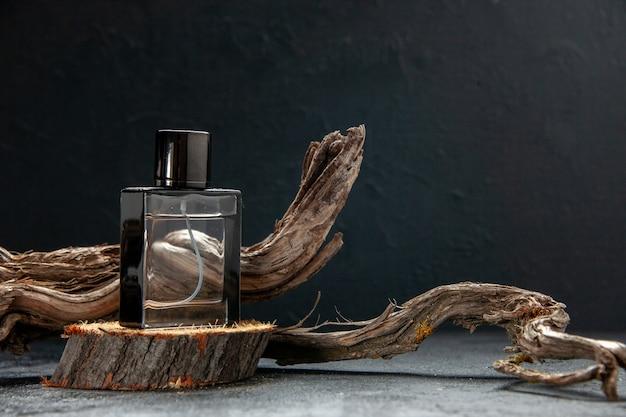 Vista frontale del profumo su tagliere di legno e ramo di albero su luce su sfondo scuro con spazio libero