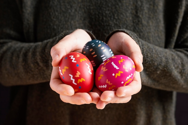 Vista frontale della persona che tiene le uova di pasqua dipinte variopinte