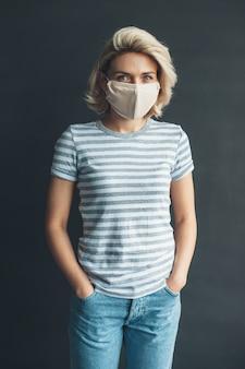 Foto di vista frontale di una donna con maschera medica sul viso che propone alla macchina fotografica in un abbigliamento casual su un muro di studio grigio scuro