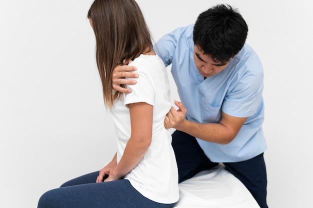 Vista frontale del fisioterapista che massaggia la schiena del paziente femminile