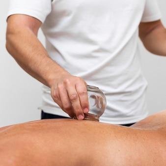 Vista frontale del fisioterapista utilizzando il metodo di coppettazione sulla schiena del paziente femminile
