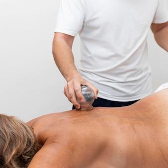 Vista frontale del fisioterapista utilizzando il metodo di coppettazione sulla schiena del paziente