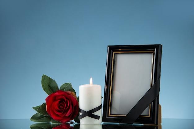 Vista frontale della cornice con candela e fiore rosso su superficie blu morte malvagia funerale