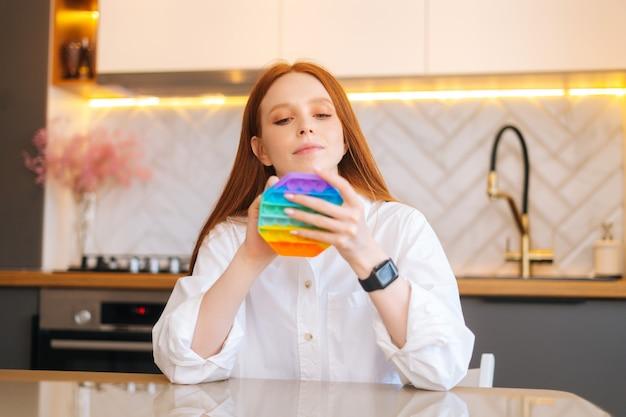 Ritratto di vista frontale di una giovane donna rossa attraente che gioca a fidget toy nuovo giocattolo in silicone alla moda
