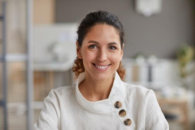 Ritratto di vista frontale di bella donna adulta che sorride alla macchina fotografica mentre lavora nell'ufficio, spazio della copia