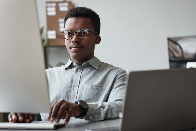 Vista frontale ritratto di giovane uomo afro-americano che utilizza computer e scrive codice nell'ufficio di sviluppo software, copia spazio