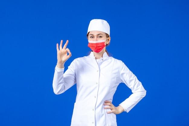 Vista frontale in posa giovane infermiera in tuta medica con maschera protettiva rossa sull'azzurro