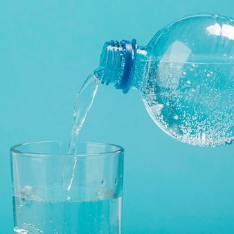 Vista frontale versando acqua frizzante in vetro