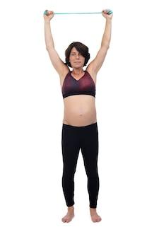 Vista frontale di una donna incinta in piedi facendo bande di resistenza all'esercizio su sfondo bianco