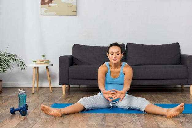 Vista frontale della donna incinta, allenamento a casa sulla stuoia con bottiglia d'acqua e pesi