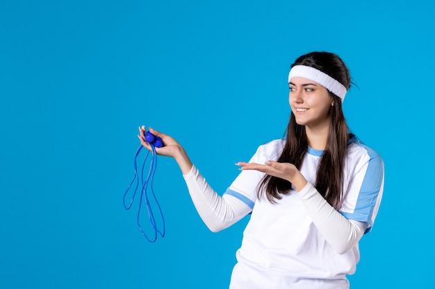 Vista frontale piuttosto femmina tenendo la corda per saltare sul blu