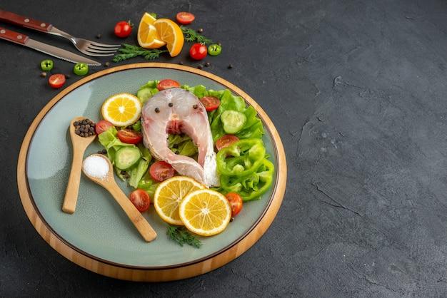 Vista frontale di pesce crudo e verdure fresche tritate fette di limone spezie su un piatto grigio e posate su superficie nera in difficoltà