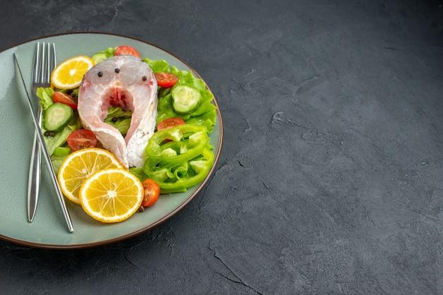 Vista frontale di pesce crudo e verdure fresche fette di limone e posate su un piatto grigio sul lato destro su superficie nera con spazio libero