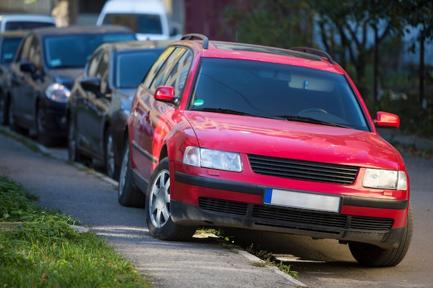 Vista frontale della macchina rossa parcheggiata parzialmente sul marciapiede su una lunga fila di veicoli diversi lungo la strada sulla soleggiata giornata autunnale. trasporti, stile di vita moderno della città, concetto di problema di parcheggio.
