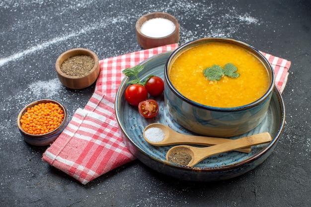 Vista frontale della zuppa di lenticchie rosse in una ciotola servita con pomodori verdi pepe sale su vassoio blu su asciugamano rosso spogliato e spezie diverse su sfondo bianco nero