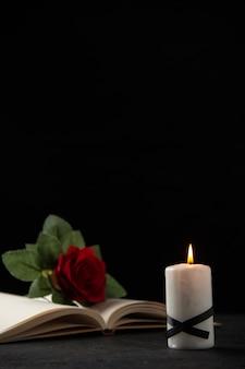 Vista frontale della rosa rossa con libro e candela su nero
